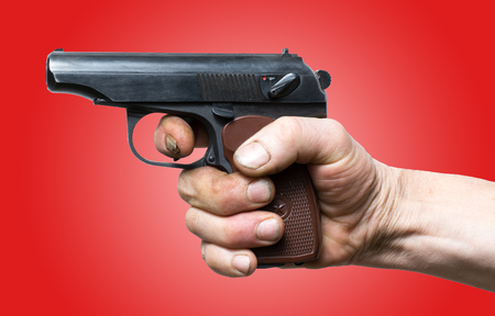 Handgun ready to fire.  Pistol in hand over red background Imagens