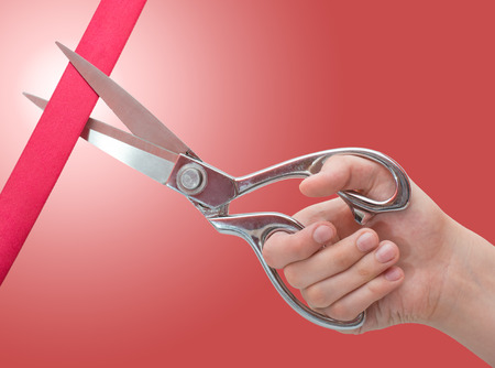 Hand with scissors cutting a red ribbon. Grand opening concept Imagens