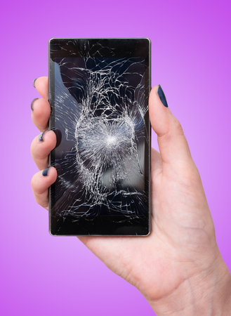 Female hand holding a mobile smart phone with cracked screen