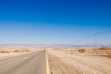 Desert road stretching into distance photo