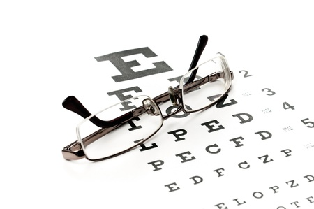 Gafas de lectura con la carta del ojo aislado en blanco Foto de archivo