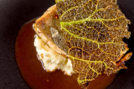 Sturgeon, savoy cabbage, mushrooms broth, mashed potato with butter on a white plate