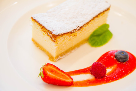 Traditional polish cheesecake served with fruit and sauce