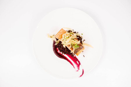 Baked salmon, beetroot mousse, black lentils and pear on a white background