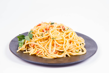 Spaghetti Carbonara with some parsley on a black plate