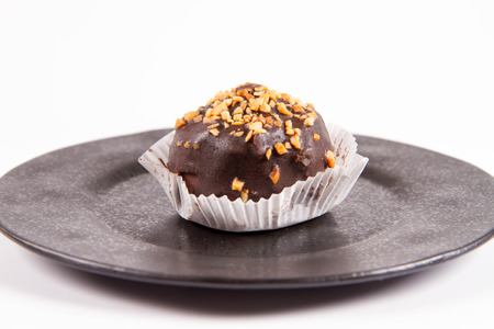 Rum ball decorated with chocolate and nuts on a black plate