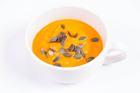 Pumpkin soup with pumpkin seeds in a bowl on a white background Фото со стока