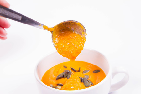 Pumpkin soup decorated with pumpkin seeds being poured into a bowl