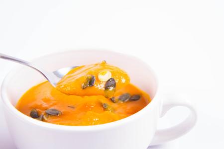 Pumpkin soup decorated with pumpkin seeds being eaten on a white background Standard-Bild