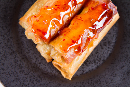 Chinese Traditional Spring rolls with sweet and sour sauce on a black plate Stockfoto