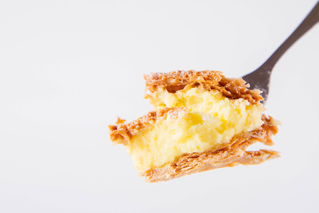 Napoleon cake - a Polish type of cream pie - sprinkled with powdered sugar, on a fork Imagens