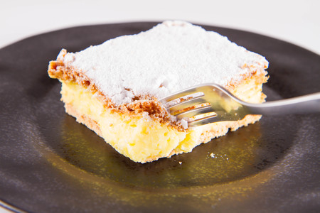 Napoleon cake - a Polish type of cream pie - sprinkled with powdered sugar, eaten with a fork Stock fotó