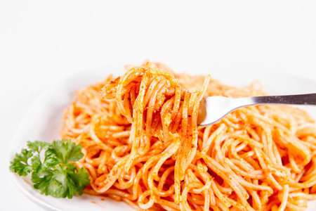 Spaghetti with pesto rosso decorated with parsley onions on a white background 免版税图像