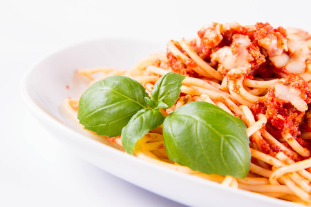 Spaghetti bolognese with melted parmesan cheese and basil on a white background