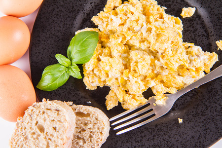 Scrambled eggs, wholemeal bread, and a fork, decorated with basil, on a white background
