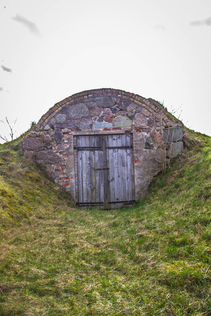 Old dug-out building under a cloudy sky Stock Photo