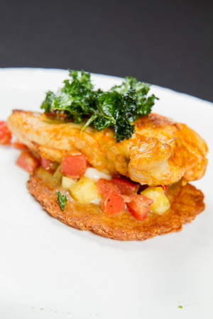 Roasted chicken served with potato pancake, pineapple, Italian cheese and cherry tomatoes
