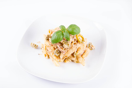 Pasta - penne with tomato sauce and jalape?o peppers on a plate, decorated with fresh basil
