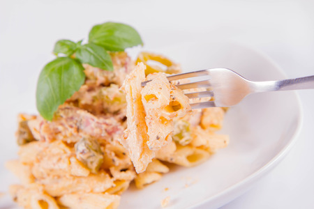 Pasta eaten with a fork - penne with cream sauce and jalapeno peppers on a plate, decorated with fresh basil