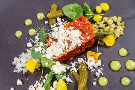 Tartar from rustic raspberry tomatoes with capers, lovage oil and wild herbs