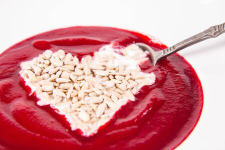 Beetroot cream soup decorated with a heart made of yoghurt and sunflower seeds eaten with a vintage spoon