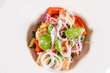 Panzanella salad with anchovies decorated with basil