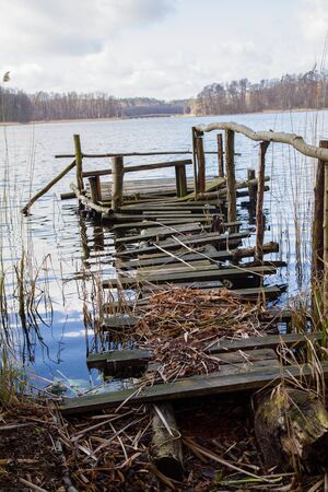 Bridge on a lakeside surrounded with reeds with another bigger bridge seen in the distance