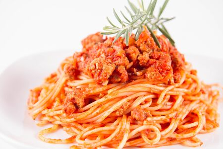 Spaghetti bolognese on a plate decorated with a rosemary twig