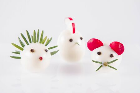 Easter holiday concept: Eggs shaped like animals (with elements made of rosemary, radish, chive) on a white background