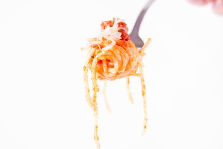 Spaghetti bolognese sprinkled with cheese on a fork on a white background