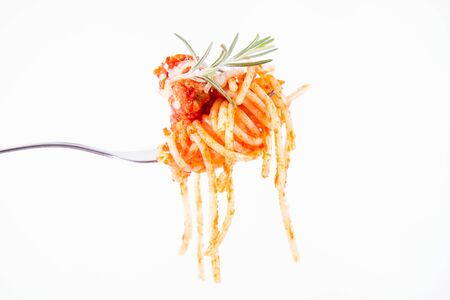 Spaghetti bolognese sprinkled with cheese and decorated with a rosemary twig on a fork on a white background Banque d'images