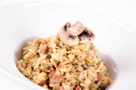 Risotto with button mushroom and bacon decorated with mushroom on a plate on a white background Banque d'images
