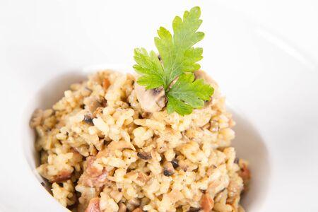 Risotto aux champignons de Paris et bacon décoré de persil sur une assiette sur fond blanc