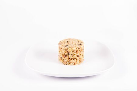 Risotto with button mushroom and bacon on a plate on a white background