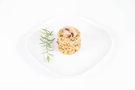 Risotto with button mushroom and bacon decorated with a mushroom and rosemary twig on a plate on a white background