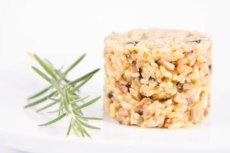 Risotto with button mushroom and bacon decorated with rosemary twig on a plate on a white background