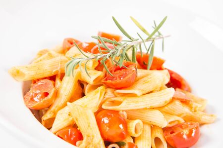 Penne with tomatoes, garlic and mozzarella decorated with rosemary twig, on a white background