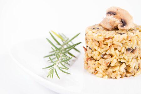 Risotto aux champignons de Paris et bacon décoré de brindille de romarin sur une assiette sur fond blanc Banque d'images