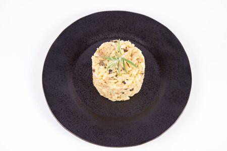 Risotto aux champignons de Paris et bacon décoré de brindilles de romarin sur une plaque noire sur fond blanc Banque d'images