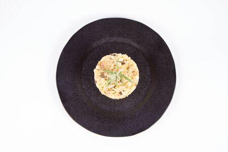 Risotto aux champignons de Paris et bacon décoré de brindilles de romarin sur une plaque noire sur fond blanc
