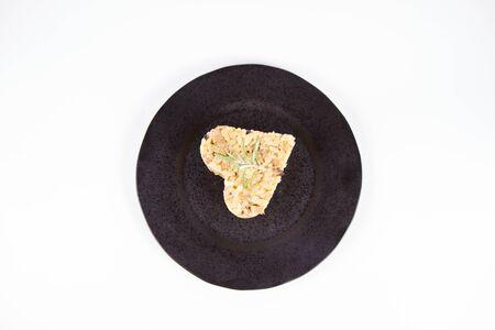 Partie en forme de coeur de risotto aux champignons de Paris et bacon décoré de brindilles de romarin sur une plaque noire sur fond blanc