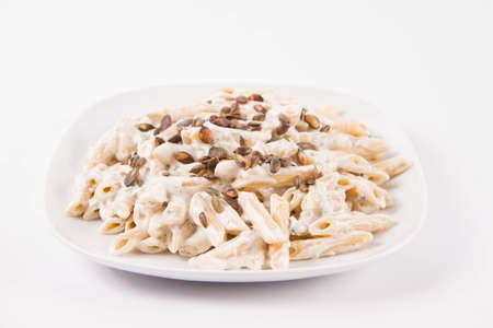 Pasta with blue cheese and cream sauce, sprinkled with roasted pumpkin seeds