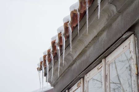 Icicles hanging from a roof over a window Banque d'images