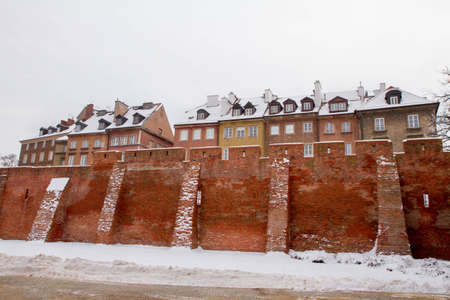 Warsaw, Poland: view of the Old Town with a part of the ancient city walls of Warsaw in the foreground