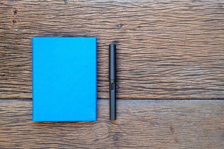 Een blauwe notebook en vulpen op hout