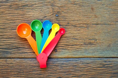 measuring spoons: Colorful plastic measuring spoons on wood