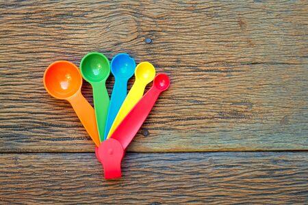Kleurrijke plastic metende lepels op hout Stockfoto - 46412725