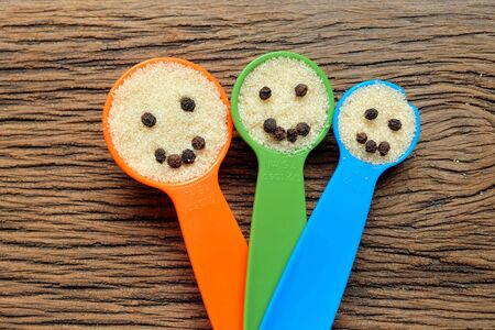 measuring spoons: Happy family faces of  plastic measuring spoons on wood with  sugar and pepper seeds