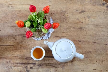 Chinese theepot en kunstmatige aardbeien op hout