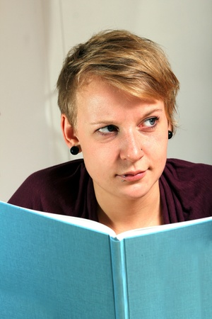 critically looking girl is reading a book photo